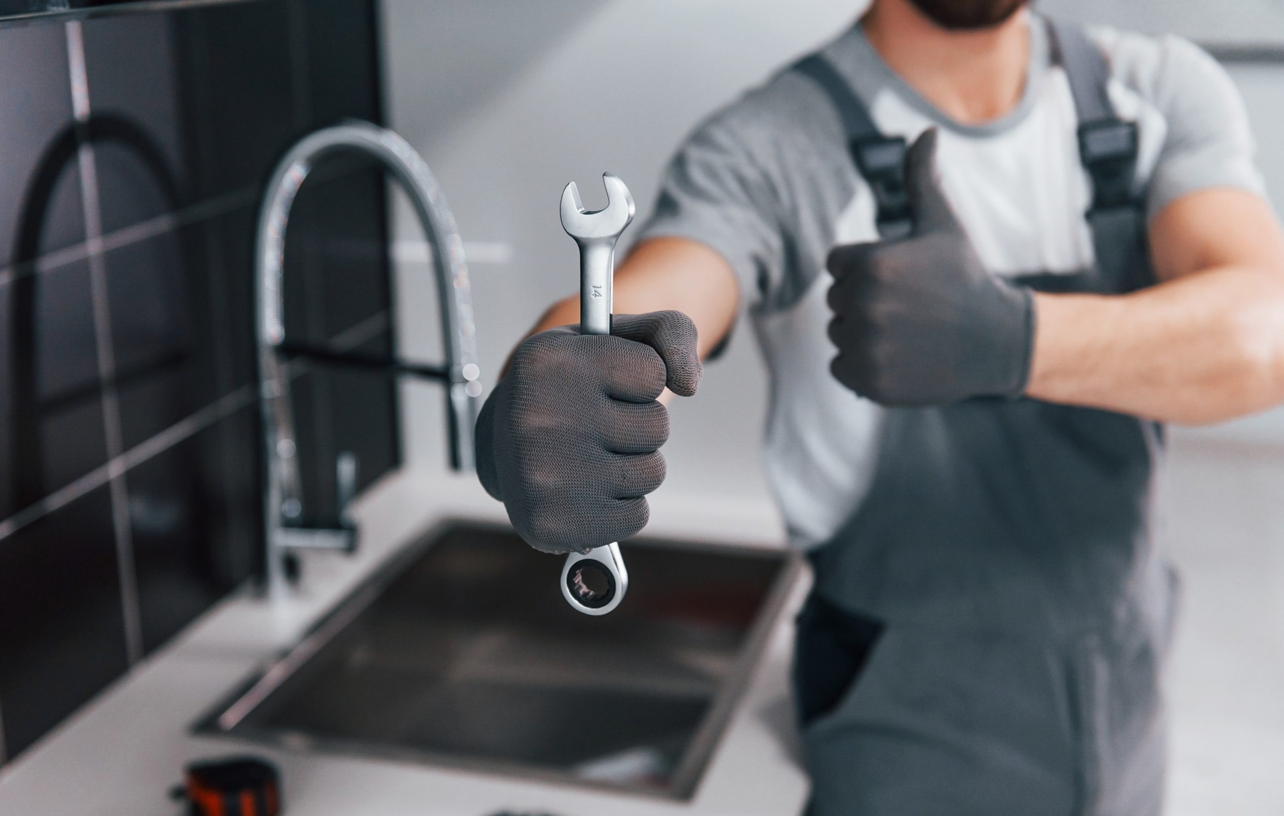 Close up view of young professional plumber in grey uniform holding wrench in hand on the kitchen