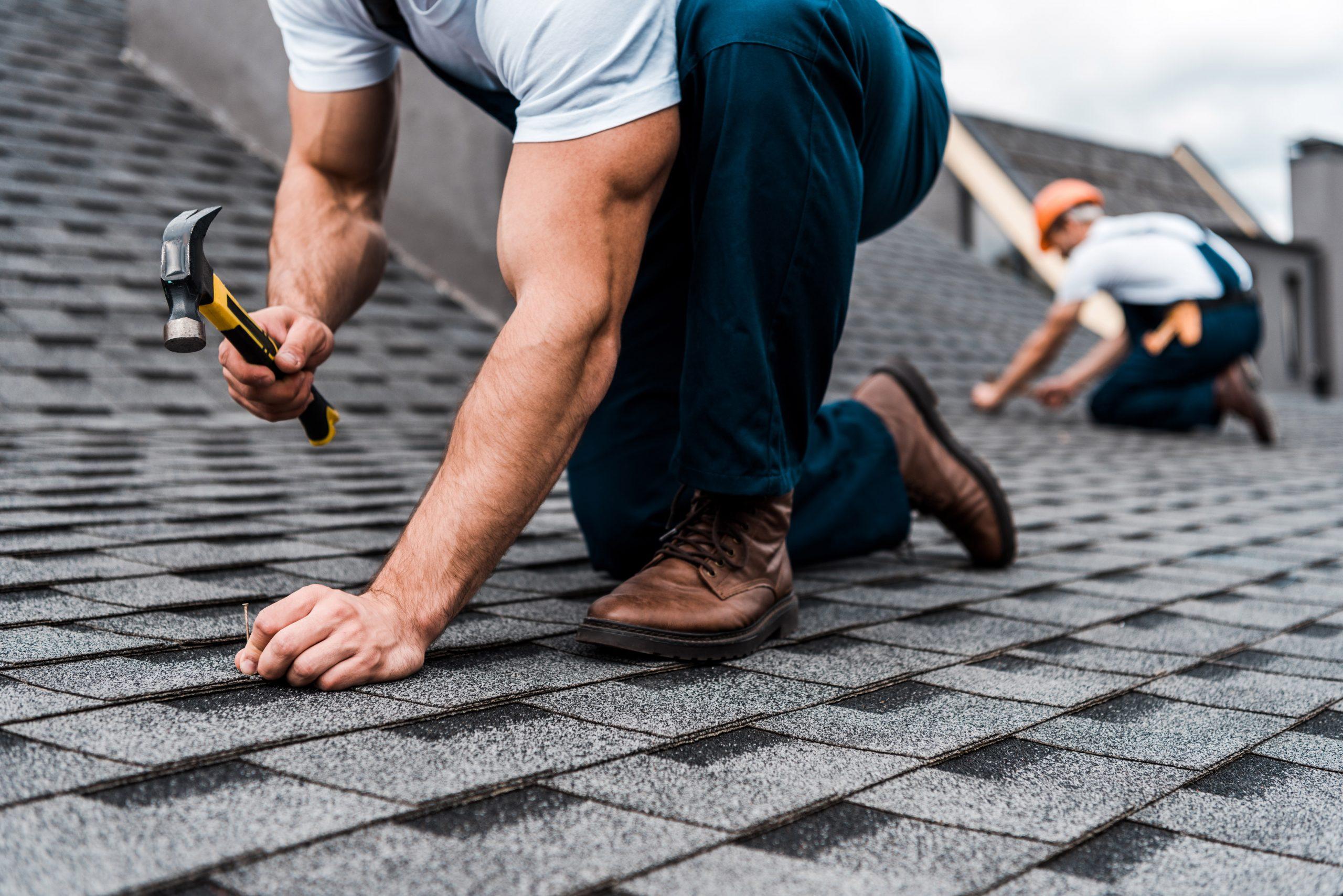 cropped view of repairmen in uniform working on rooftop
