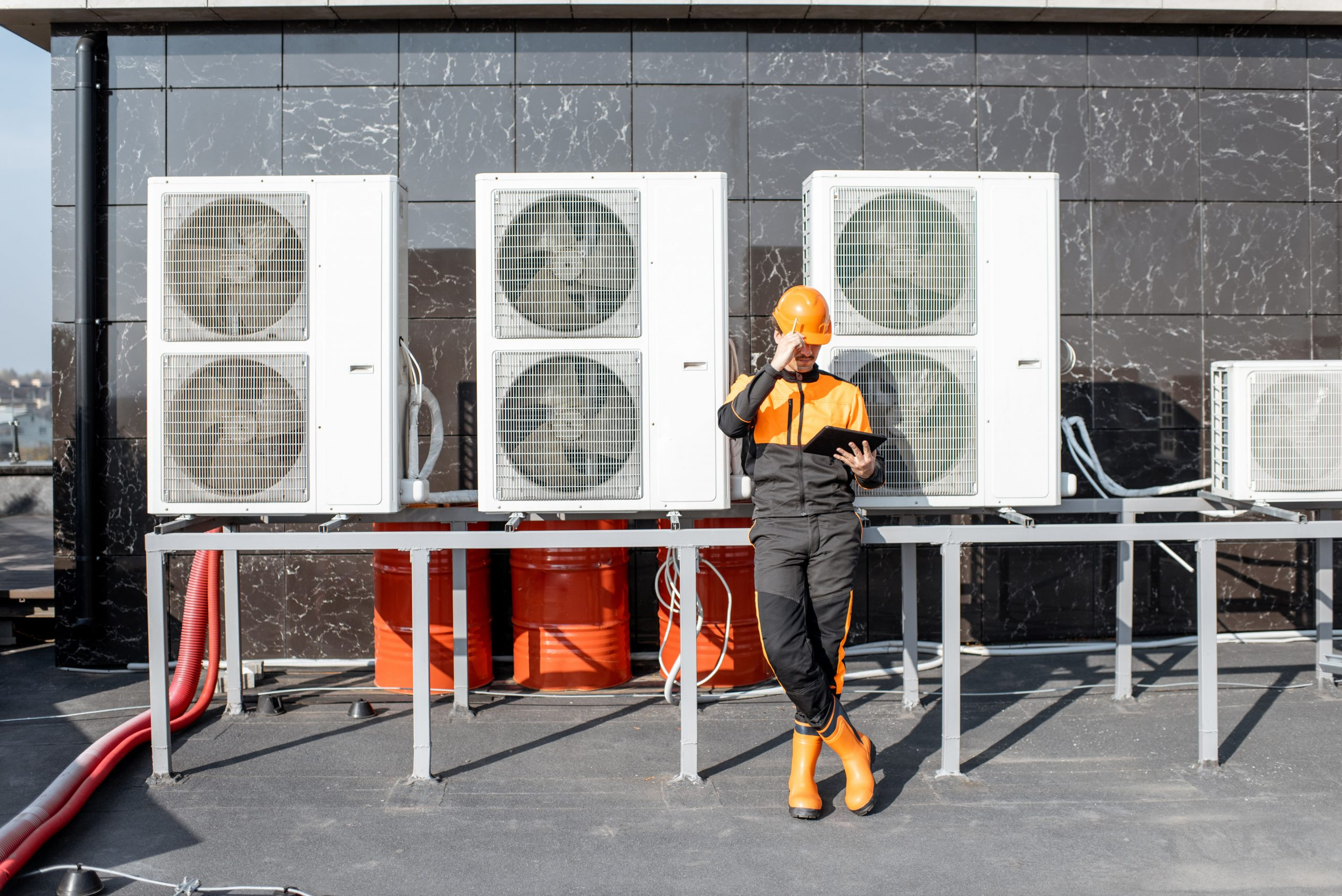 Workman servicing air conditioning or heat pump with digital tablet