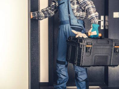 Door to Door Service Concept. Professional Technician with His Tools Box Entering Apartment. Call For Assistance.